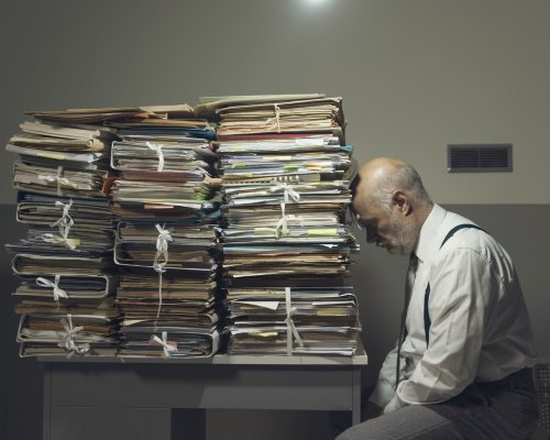 A man is overwhelmed by the quantity of paper documents he has to go through