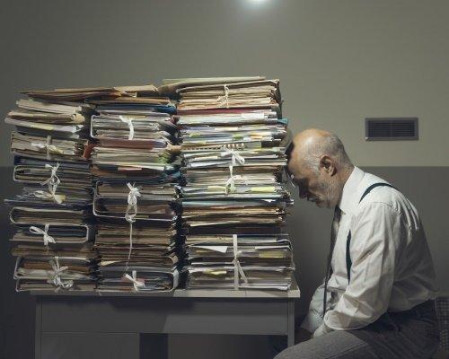 Un homme est découragé par la quantité de papier qu'il a à traiter.