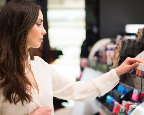 A woman is inspecting different cosmetic products on a shelf to make her decision.