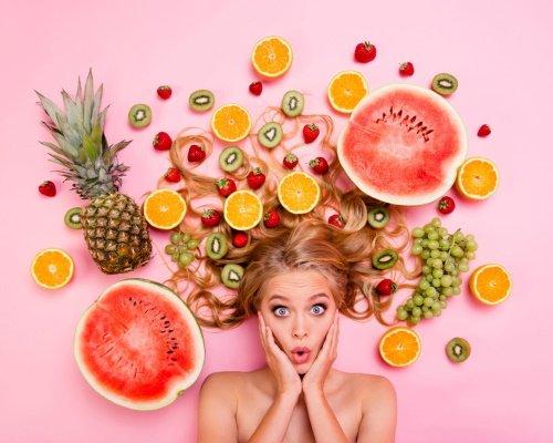 Une femme est entourée de fruits exotiques, représentant sa créativité.